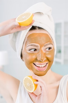 Beauty skin care concept. pretty caucasian woman in white towel with brown mud facial mask on face holds citrus fruit on her hand on light space. spa procedures and mask on skin