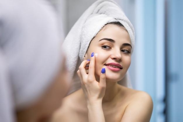 Bellezza, cura della pelle e concetto di persone - giovane donna sorridente che applica la crema sul viso e guarda allo specchio nel bagno di casa