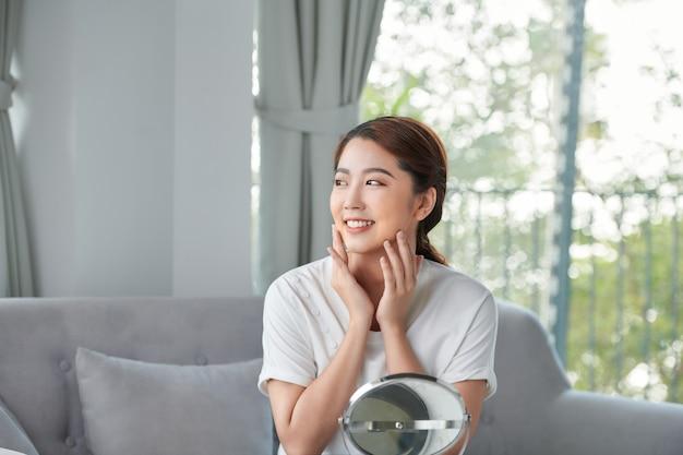 美容スキンケア。彼女のきれいな肌を楽しんで、鏡の前で彼女の顔に触れている若い美しいアジアの女の子。