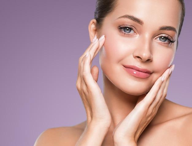 美容肌の女性の顔が健康な髪の化粧品ナチュラルメイクハッピーモデルマニキュアネイルハンドを閉じます