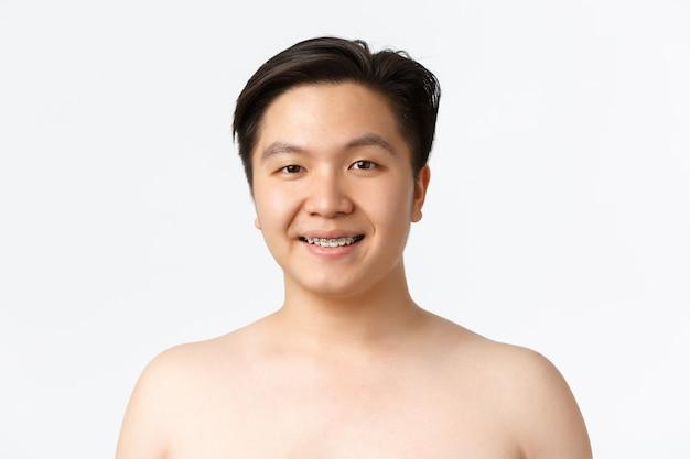 뷰티 스킨케어 및 위생 개념은 교정기에 알몸으로 서 있는 웃고 있는 아시아 남자의 근접 촬영입니다.
