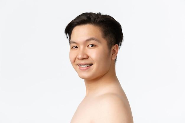 裸のオベに立っている中かっこで笑顔の裸のアジア人男性の美容スキンケアと衛生コンセプトのクローズアップ...
