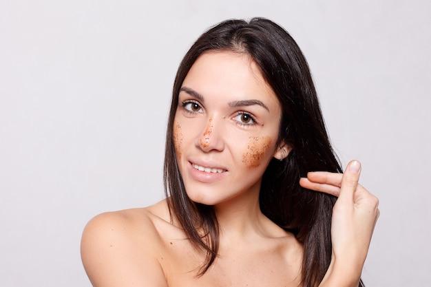 美容、スキンケア、人々の概念-彼女の顔に茶色のスクラブをしている女の子のクローズアップの肖像画は、白い背景の孤立した肌を剥がしています。彼女の顔に触れる美しいスパの女性。完璧なフレッシュスキン。