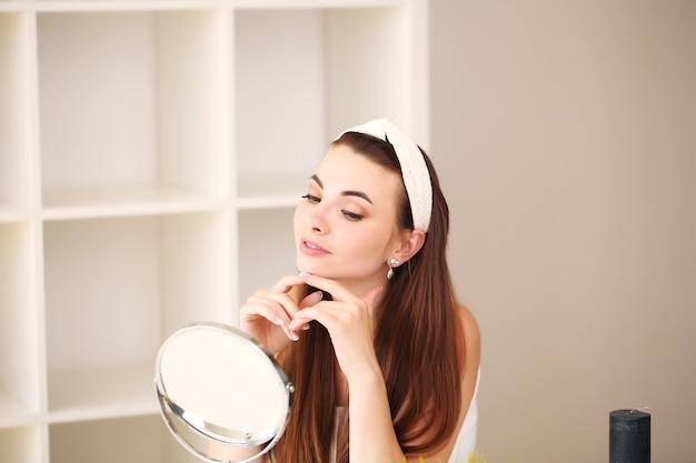 美容、スキンケア、人々のコンセプト-部屋の顔に美容を提案する笑顔の若い女の子。