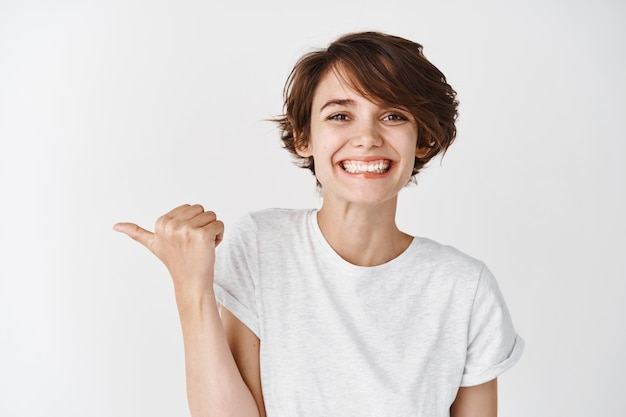 Beauty and skincare. beautiful caucasian woman with short hair, wearing t-shirt, smiling and pointing left, standing against white wall