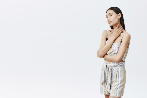 Beauty, skincare and body concept. portrait of sensual and gentle asian female in stylish outfit standing half-turned in relaxed pose with closed eyes, touching neck and feeling comfort
