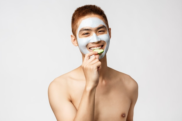 Beauty, skincare and spa concept. handsome asian man with naked torso in cosmetic facial mask, eating cucumber and smiling, relaxing on leisure at salon, standing white wall