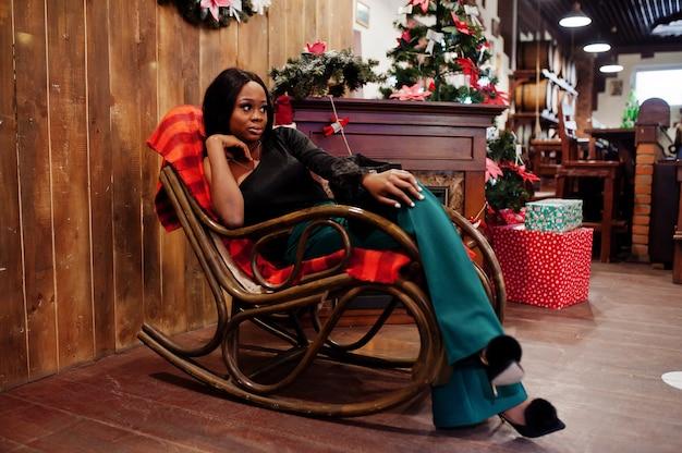 花輪、暖炉、ロッキングチェアを備えたクリスマスムードの装飾に対してポーズをとった黒のブラウスと緑のロングレッグパンツの美しさのスリムなアフリカ系アメリカ人モデルの着用。