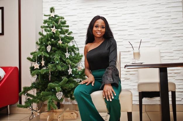 カフェでポーズをとった黒のブラウスと緑のロングレッグパンツに美スリムなアフリカ系アメリカ人モデルが着て、新年のツリーに対してラテコーヒーを飲みます。クリスマス気分。