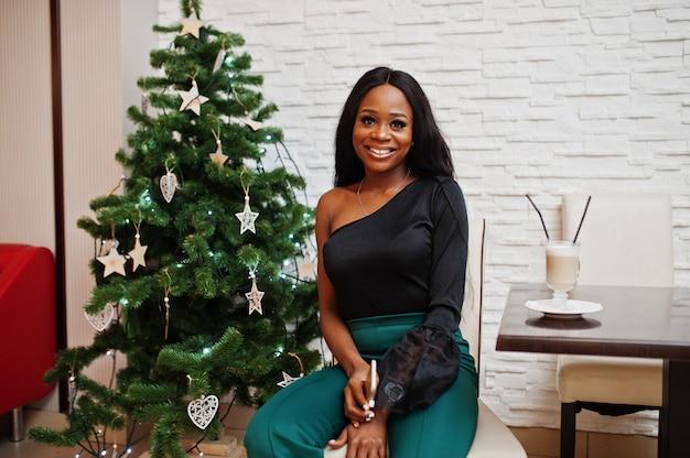 Красавица стройная афро-американская модель носит черную блузку и зеленые длинные штаны, позирует в кафе и пьет латте с мобильным телефоном на фоне новогодней елки.