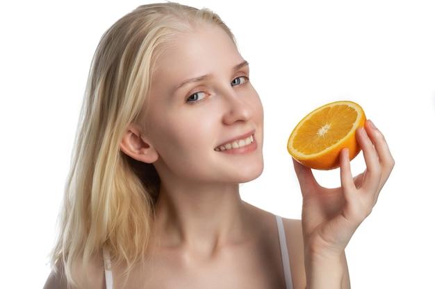 Красота. улыбающаяся женщина с сияющей кожей лица и оранжевым портретом. красивая улыбающаяся девушка-модель с естественным макияжем, здоровой улыбкой и сияющей увлажненной кожей лица. концепция косметики с витамином с