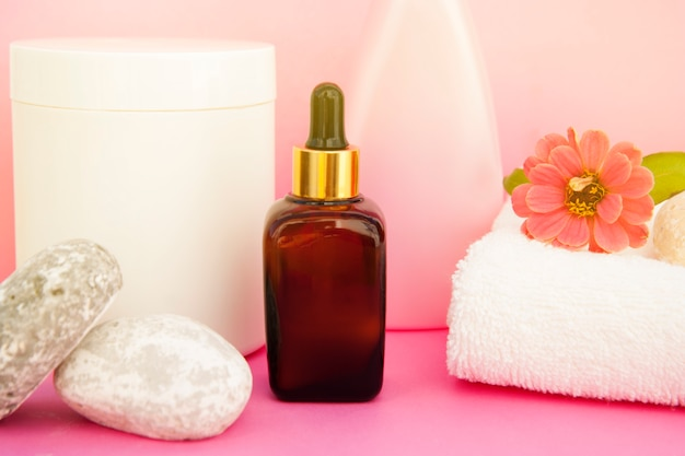 Beauty spa cosmetics, salon therapy . glass bottle on pink .
