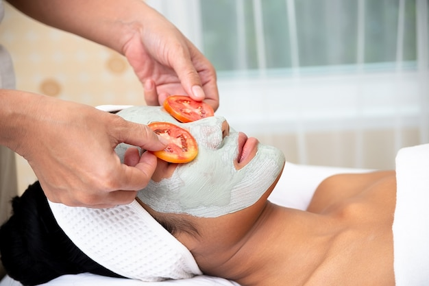 Beauty spa face with facial clay mask and tomato
