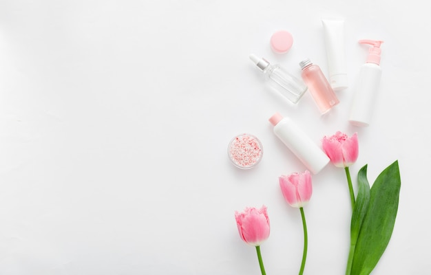 Beauty spa medical skincare bath pink products with flowers. cosmetic bottles, tubes, dispenser, dropper, serum cream packaging.