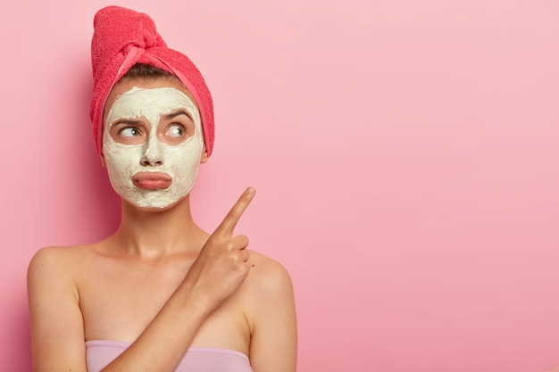 Beauty, spa, treatment concept. unhappy dissatisfied woman purses lips, applies clay mask for rejuvenation, wrapped in bath towel, points on copy space against pink wall, wants fast result