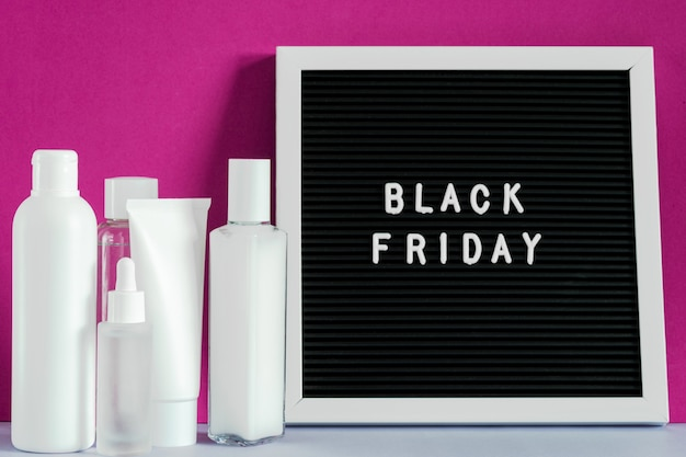 Beauty spa treatment skincare cosmetic cream facial  tube container product packaging on purple background, black friday on letter board. cosmetic discount concept