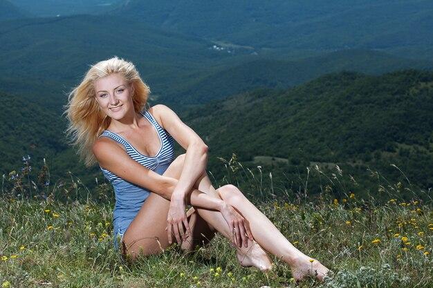 山でエクササイズをしている美容スポーティな女性