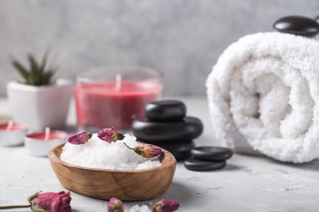 Beauty still life of massage oil bottle of aroma essential   and natural fragrance salt with stones, candles on concrete grey table. composition of spa treatment