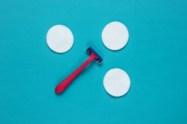 Красота натюрморта, минимализм. пластиковая бритва-эпилятор с хлопковыми кружками на синем фоне. женские аксессуары для ухода за красотой.