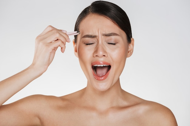 Beauty of stressed young woman with brown hair screaming in pain while plucking eyebrows using tweezers, isolated over white