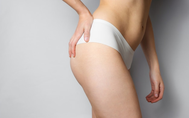 뷰티 스튜디오 촬영. 흰색 팬티에 슬림 한 여자가 회색에 그녀의 엉덩이를 만지