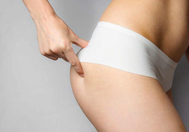 Beauty studio shot. slim woman in white panties touches her elastic buttocks on gray. crop photo