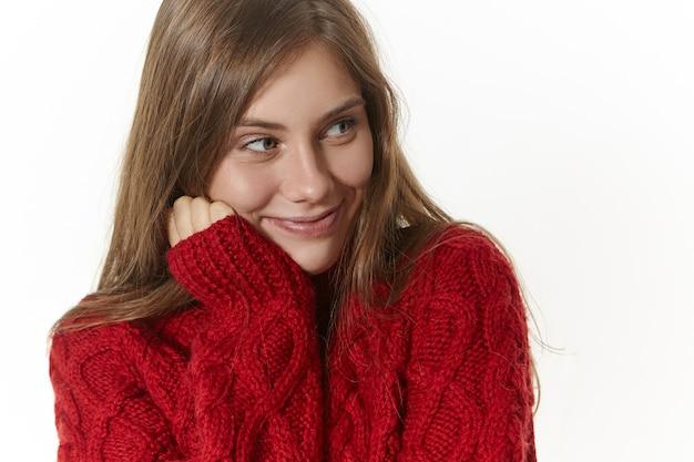 美しさ、スタイル、ファッションのコンセプト。頬に手をつないで、好奇心旺盛な笑顔で目をそらし、面白い話を注意深く聞いて、居心地の良い長袖のセーターを着た魅力的な遊び心のある若い女性