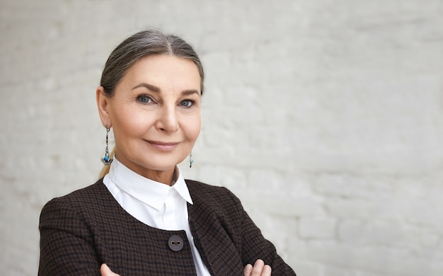 Beauty, style, fashion and age concept. close up portrait of positive elegant 60 year old female with gray hair and wrinkled face posing against white brick wall