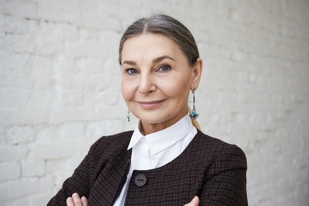 아름다움, 스타일, 패션 및 연령 개념. 회색 머리와 흰색 벽돌 벽에 포즈 주름진 얼굴 긍정적 인 우아한 50 세 여성의 초상화를 닫습니다