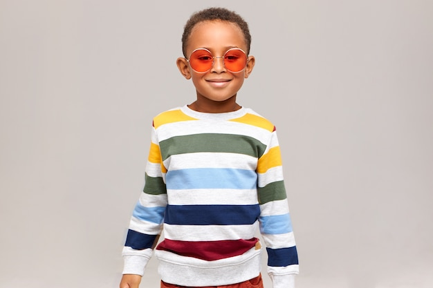 Beauty, style and fashion concept. picture of cheerful fashionable african boy posing isolated wearing stylish striped sweater and trendy round pink sunglasses, smiling happily