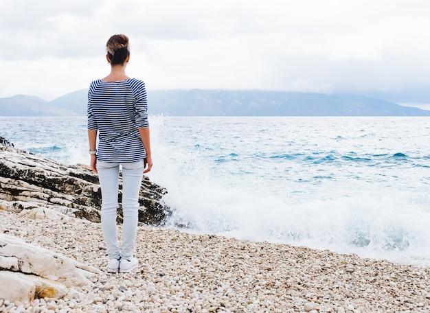 美しくスタイリッシュな若い女性は、曇りの夏の日に海辺の小石の石の海岸に立って目をそらすのを楽しんでいます。
