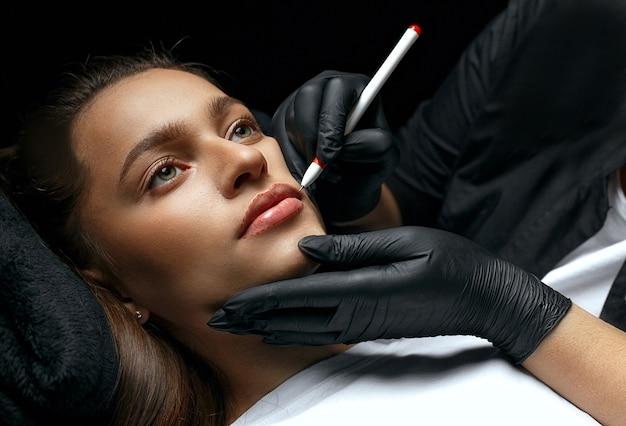 Стилист делает форму губ перед процедурой перманентного макияжа в косметическом салоне