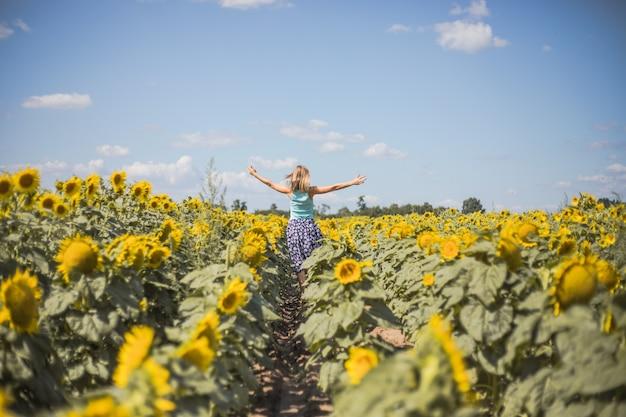黄色いひまわり畑の美しさ太陽に照らされた女性自由と幸福の概念。幸せな女の子の屋外
