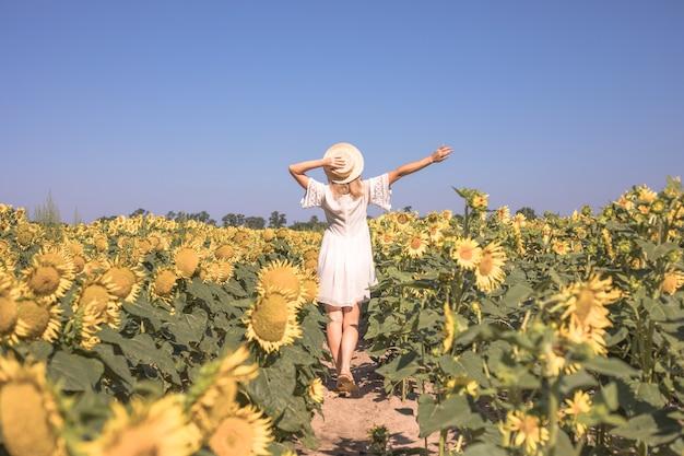黄色いひまわり畑の美しさの太陽に照らされた女性自由と幸福の概念屋外で幸せな女の子