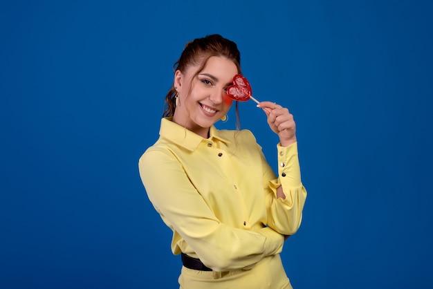 Удивленная красота молодая фотомодель девушка с печеньем в форме сердца в руке.