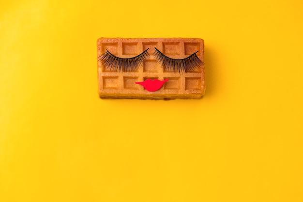 黄色の背景に化粧と美しい甘いウィーンのワッフル。ミニマリストスタイル。創造的なアイデア