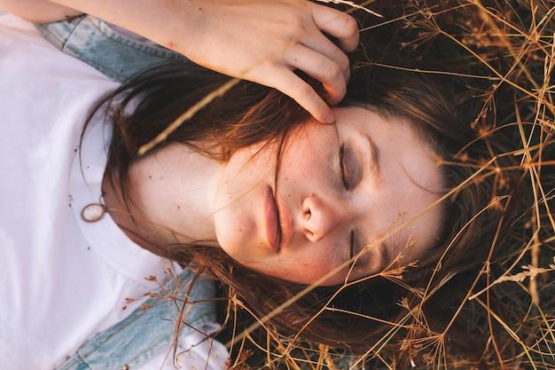 太陽の光の秋のフィールドで自然を背景に茶色の髪の美しさの10代の少女