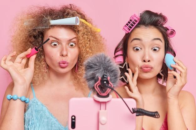 팔로워를 위한 뷰티 팁. 놀란 여성들이 스마트폰 카메라를 보고 있다