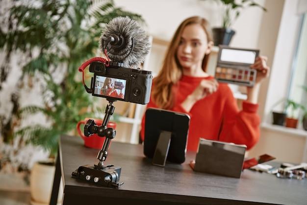 비디오 리뷰를 녹화하는 동안 카메라에 메이크업 팔레트를 보여주는 뷰티 팁 젊은 매력적인 여성