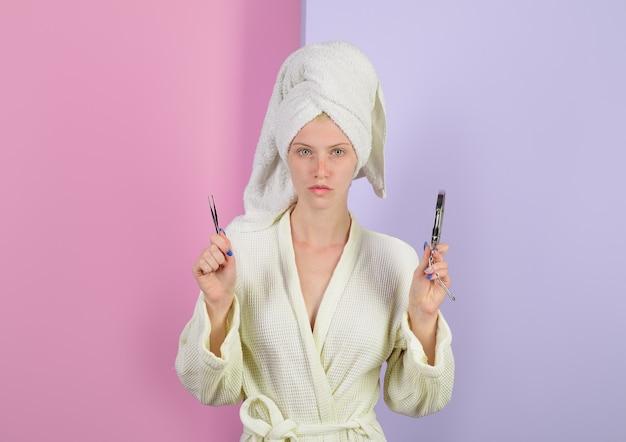 미용 도구 여성은 미용실 제모 눈썹에서 핀셋과 거울 교정 절차를 보유하고 있습니다.