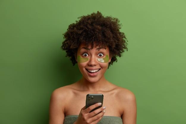 집에서 미용 치료. 긍정적 인 어두운 피부를 가진 여자는 목욕 타월에 싸여 있고 콜라겐 패치를 적용하고 메시지에 좋은 소식을 듣게되어 행복하며 녹색 벽에 고립 된 스마트 폰을 보유하고 있습니다.