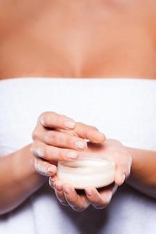Косметические процедуры. обрезанное изображение женщины, завернутой в полотенце, принимая сливки из контейнера
