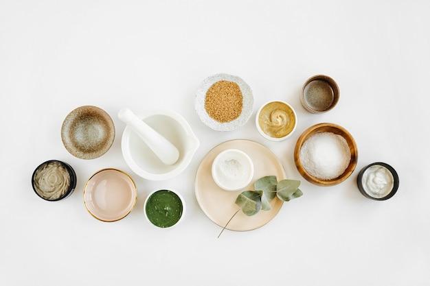 Ингредиенты для косметических процедур для приготовления домашней косметической маски по уходу за кожей. различная чаша с глиной, сливками, эфирным маслом и натуральными ингредиентами на белом фоне стола. органическая косметическая продукция для спа