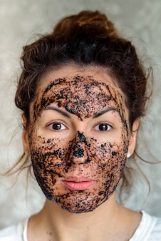 Косметический уход молодой девушки с маской скраб на лице