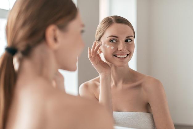 Косметические процедуры. вид через плечо молодой красивой молодой женщины, намазывающей крем на лицо, глядя в зеркало