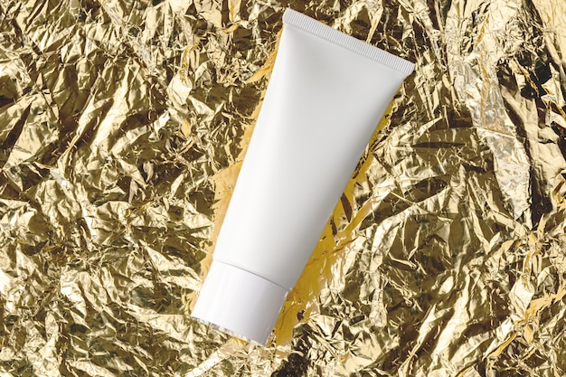 Beauty treatment skincare and cosmetic lotion cream oil  bottle packaging product flat lay.  white tube for moisturizer, facial cleanser, shampoo on golden crumpled metal texture top view