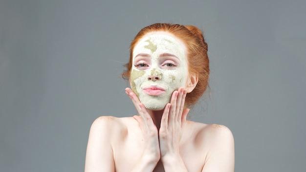 Косметические процедуры. девушка наносит маску из зеленой глины для лица. эстетическая процедура