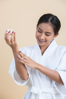 Beauty treatment with woman holds a moisturizer in her hand