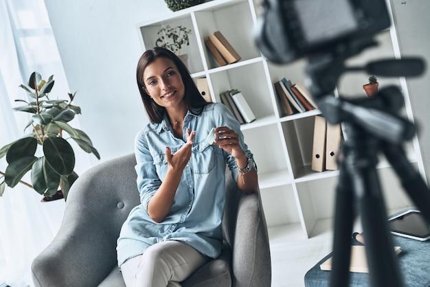 美容トリック。屋内で新しいビデオを作りながら美容製品を見せている魅力的な若い女性