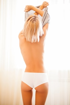 美容脱衣。カメラに立ち返りながら脱いでいる美しい若いブロンドの髪の女性の背面図